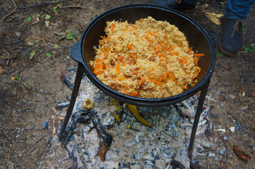 Meat with rice and carrot in a cauldron over a bonfire