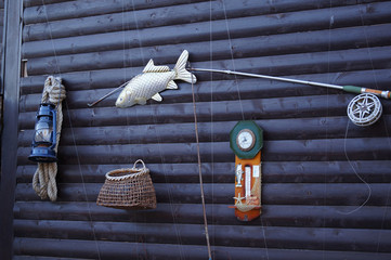 Fishing tools hanging on the dark wood wall. Set of equipment with rod, fish, barometer, basket and lantern with rope
