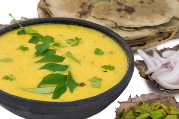 Rajasthani And Gujarati Traditional Cuisine Kadhi or Bajra Roti with Fried Chili, Onion or Lemon - Indian Vegetarian Curry Made of Buttermilk And Chick Pea Flour. Cuisine isolated on White Background