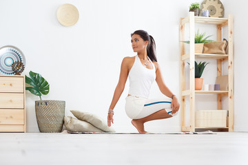 Beautiful young fit woman in a sport suit doing warm-up before yoga at home