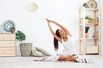 Printed roller blinds Yoga school Charming young female yoga instructor doing a lotus posture at the beginning of a complex of exercises sitting on rug in modern interior