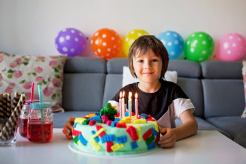 Cute child, boy, celebrating his birthday with colorful cake, candles, balloons