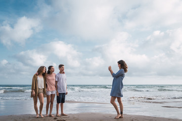 Mother taking picture of her children on beach