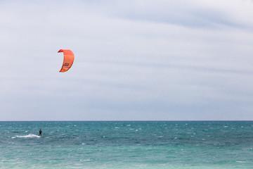 Professional Kitesurfer / Kitesurfing in the Mediterranean sea practicing with his Kiteboarding in the blue sea of the Mediterranean in the middle of winter