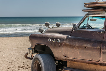 Big Rusted car hot rod on the beach with blue sea in the background