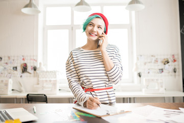 Waist up portrait of contemporary creative young woman with mint-colored hair smiling happily looking away while speaking by phone and drawing sketches standing at work table in sunlit design atelier.