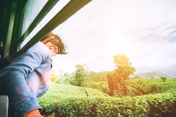 Happy woman looks out from train window during traveling on most picturesque train road in Sri Lanka