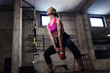 Fitness woman exercise in the gym with kettlebell.