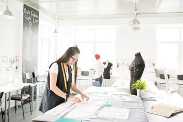 Wide angle portrait of focused Asian woman tracing patterns for custom made clothes while standing at tailors table and working in modern design atelier with people working in background, copy space