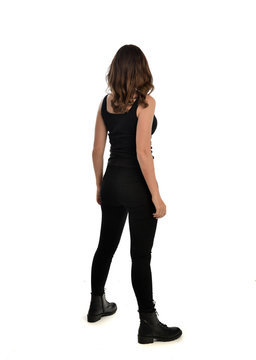 full length portrait of brunette girl wearing black singlet, jeans jeans and boots. standing pose, with back view. isolated on white studio background.