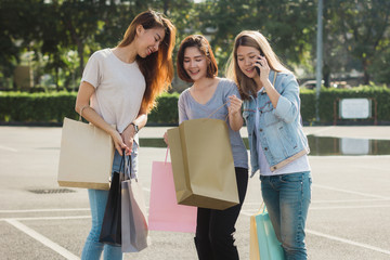 Group of young Asian Woman shopping in an outdoor market with shopping bags in their hands. Young women show what they got in shopping bag under warm sunlight. Group outdoor shopping concept.