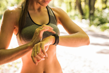 Close up of woman using activity tracker or heart rate monitor. Outdoor fitness concept.