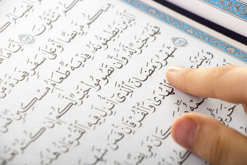 Muslim boy pointing to the word : Ramadan ( The holy Month ) while reading the Quraan in a mosque