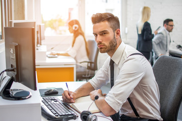 Handsome man in businesswear working on desk near computer in office