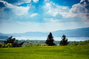 panorama of Lake Maggiore green woods around and cloudy sky with rays of light, storm approaching