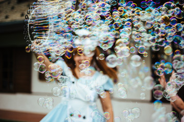 young girl produces many soap bubbles with large circle