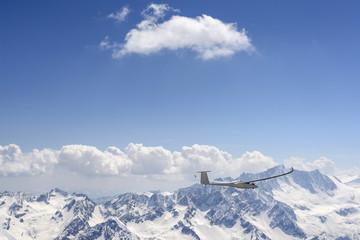 glider in flight with Presanella range in background, Italy