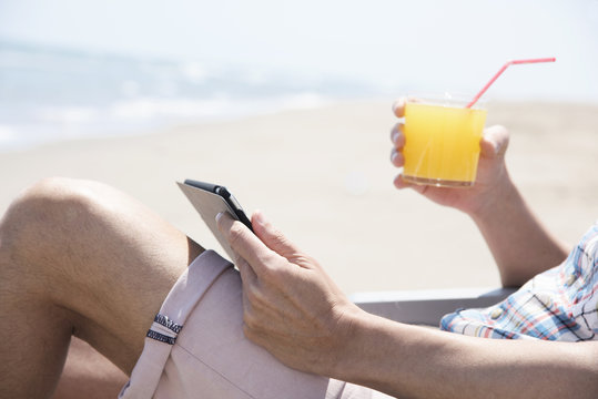 man using a tablet on the beach
