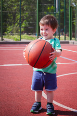 a boy of two years playing with a ball on the basketball court. Toddler boy playing basketball