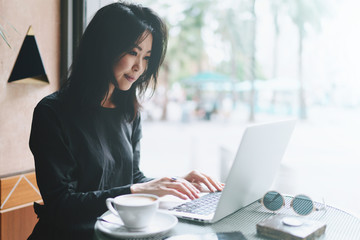 Beautiful asian female student sitting with portable laptop in modern coffee shop. Successful female freelancer using portable computer for a distance work during morning breakfast in cafe