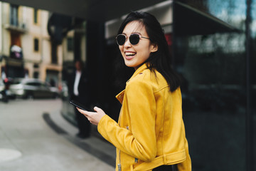 Photo in motion of a smiling asian woman with long dark hair in yellow leather jacket holding a...