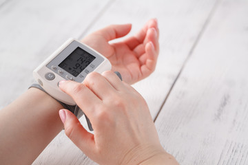 woman measures to herself arterial blood pressure, hands close-up