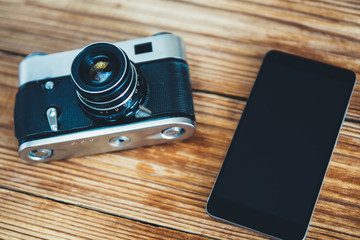 Vintage camera and modern smartphone. Amateur photography before and now