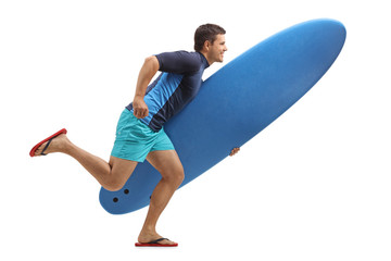 Surfer holding a surfboard and running
