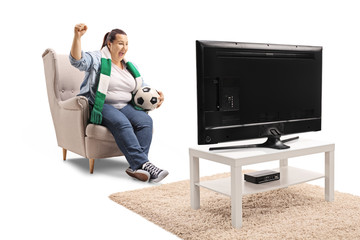 Overjoyed female soccer fan seated in an armchair watching football on TV
