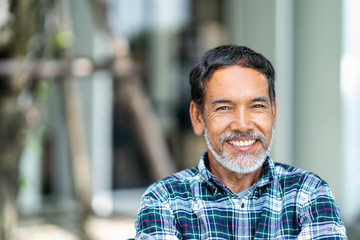 Portrait of happy mature man with white, grey stylish short beard looking at camera outdoor. Casual lifestyle of retired hispanic people or adult asian man smile with confident at coffee shop cafe. Wall mural