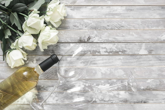 White roses and a bottle of white wine and two wine glasses on a wooden gray vintage table. Valentine's Day, 8 March, wedding, birthday. Flat lay, top view, copy space