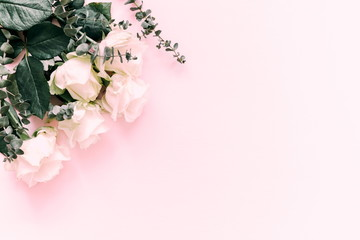 Flowers composition. Border of flowers roses and eucalyptus branches on a pink background. Flat lay, top view, copy space