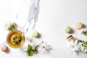 Glass cup of hot green tea with french dessert macaroons, spring flowers white magnolia and cherry blooming branches over white marble texture background. Top view, copy space.