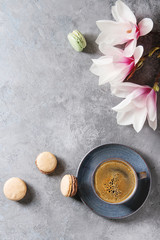 Blue cup of black espresso coffee, french dessert macaroons and spring flowers magnolia branches over grey texture background. Top view, space. Spring greeting card,