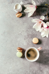 Pink mug of black espresso coffee french dessert macaroons, cream and spring flowers magnolia branches over grey texture background. Top view, space. Spring greeting card