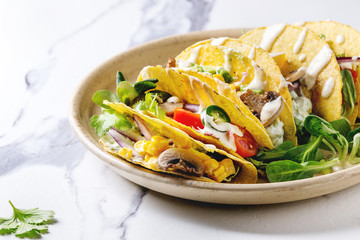 Variety of vegetarian corn tacos with vegetables, green salad, chili pepper served on ceramic plate with tomato and cream sauces with ingredients above on white marble kitchen table. Close up