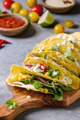 Variety of vegetarian corn tacos with vegetables, green salad, chili pepper served on wooden cutting board with tomato and cream sauces with ingredients above over grey texture background. Close up