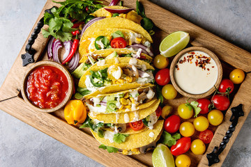 Variety of vegetarian corn tacos with vegetables, green salad, chili pepper served on wooden tray with tomato and cream sauces with ingredients above over grey texture background. Top view, space.