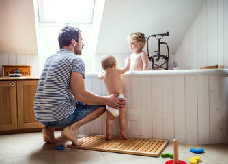 Father washing two toddlers in the bathroom at home.