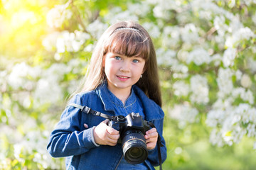 A beautiful little girl is holding a camera in her hands. A little girl takes pictures of flowers in an apple orchard at the end of a summer day.