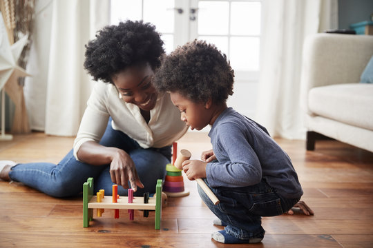 Mother And Young Son Playing With Wooden Toy At Home
