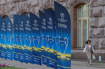 A woman walks past flags with the UEFA Champions League final logo in Kiev