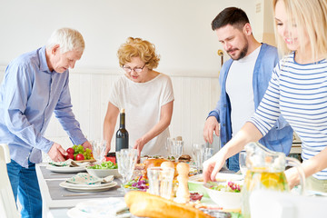 Portrait of happy two generation family preparing dinner together serving table with delicious homemade dishes for holiday  in modern sunlit apartment