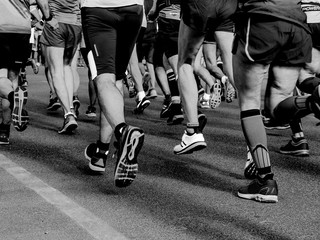 group legs runners athletes run street of city black and white image