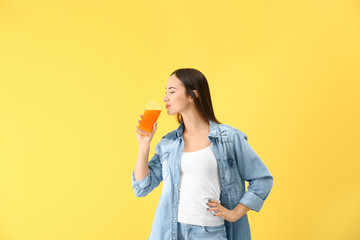 Young woman drinking orange juice on color background