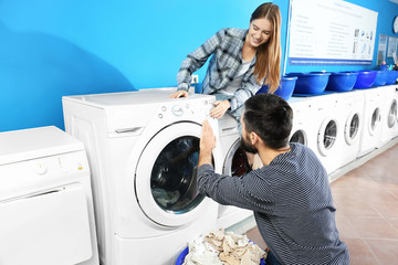 Young couple doing laundry in laundromat
