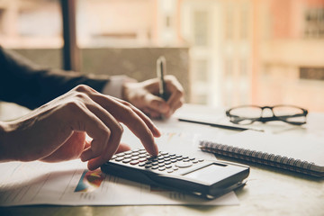 Close up hands businessman doing finances with using calculator and writing note in office.