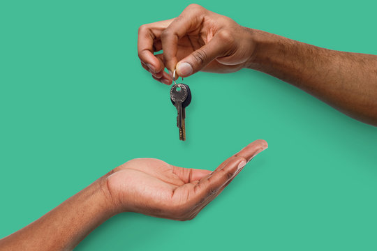 Black man handing key over to person hand