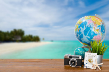Summer concept , Camera ,world map and travel accessories with Beach white sand and turquoise sea color background on the weekend holidays
