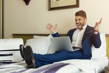 Businessman sitting on bed and using laptop
